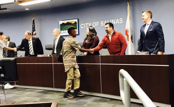Youth shaking hands with Salinas City Council Members